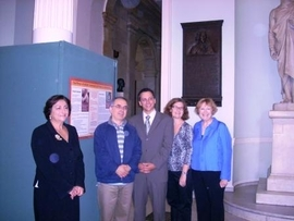 Lia Tota, Huseyin Senturk, State Representative Aaron M. Michlewitz, ESOL teachers Gretchen Yochum and Mary Ellen Happel stand in front of Huseyin's student profile in Doric Hall during a visit to the MA State House.