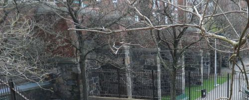 Through the trees, the granite, brick & concrete of the wall can be seen from inside the park.