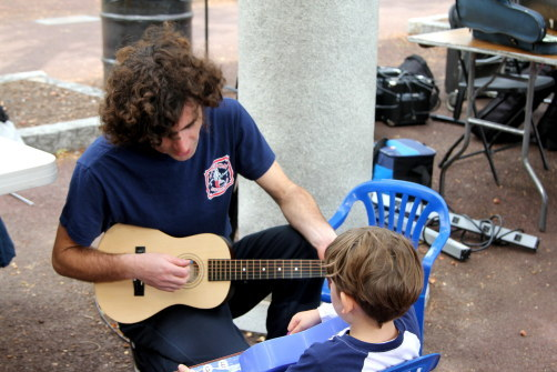 "NEMPAC's Jeremy Sarzana teaches a child at the musical ""petting zoo."" Jeremy also played later with NoEnd, the NEMPAC House Band."