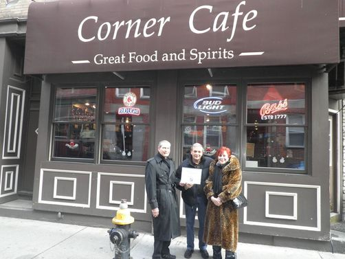 Shown (l to r) committee member Paul Nelson, Richy Loungo Café owner and committee member Janet Gilardi in front of the Corner Cafe. (Photo by Phil Orlandella.)