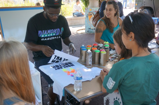 Kids watch a T-shirt being made from spray painted stencils.