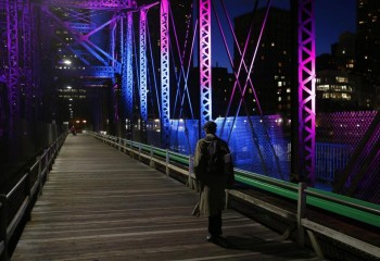 JESSICA RINALDI/GLOBE STAFF/FILE A pedestrian crosses the Old Northern Avenue Bridge one evening last May.