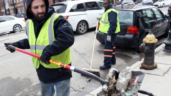 Boston Public Works employees, including Stavros Fotiadis, left, clean trash from Hanover Street in the North End, Monday, March 16, 2015. Staff photo by Angela Rowlings.